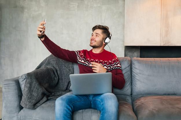 Junger attraktiver mann auf sofa zu hause im winter mit smartphone in kopfhörern, musik hörend, roten strickpullover tragend, am laptop arbeitend, freiberufler