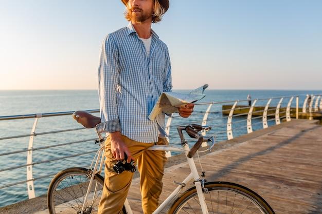 Junger attraktiver mann, der auf fahrrad durch see in den sommerferien durch das meer auf sonnenuntergang, boho-hipster-art-outfit reist, hält kartenbesichtigung, die foto auf kamera, gekleidet in hemd und hut hält