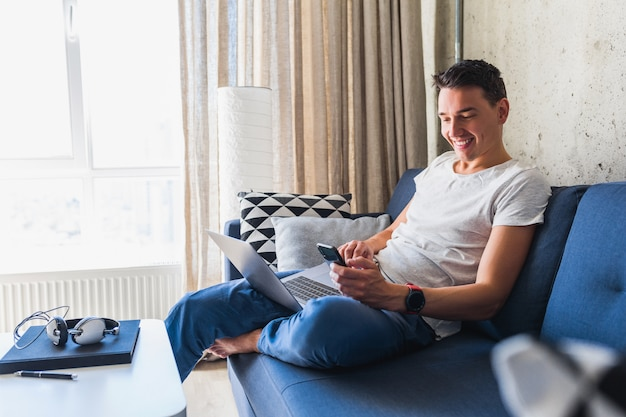 Junger attraktiver mann, der auf sofa zu hause hält smartphone hält und online am laptop arbeitet