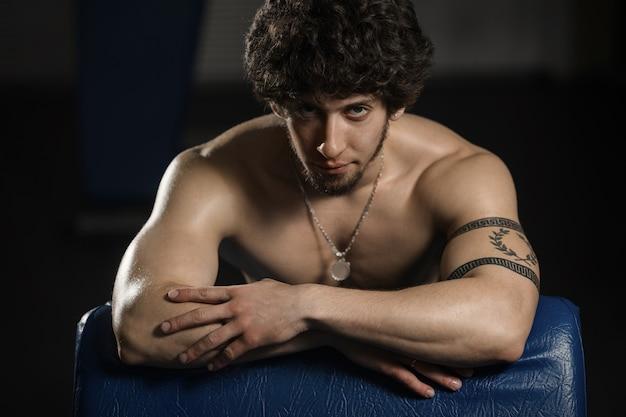 Junger attraktiver mann, der in der turnhalle nachdem dem trainieren, männliche aufstellung stillsteht