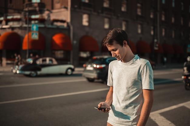 Junger attraktiver mann, der in die stadt geht und smartphone verwendet