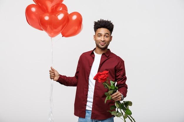 Junger attraktiver mann, der roten ballon hält und aufstand, um seine freundin zu überraschen.