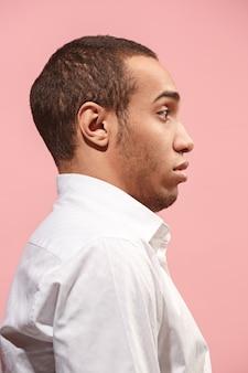 Junger attraktiver mann, der überrascht auf rosa sucht