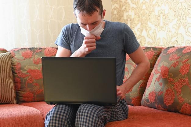 Junger attraktiver mann, der vom hauptwohnzimmer arbeitet, das auf sofa mit laptop sitzt. fernarbeitskonzept