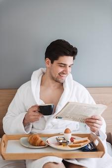 Junger attraktiver mann, der weißen bademantel trägt, der frühstück und zeitung liest, während auf bett in hotelwohnung sitzt
