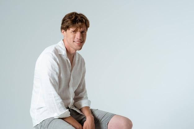 Junger attraktiver mann, der weißes hemd trägt, lächelt und betrachtet kamera, während er sitzt und auf weißer wand aufwirft.