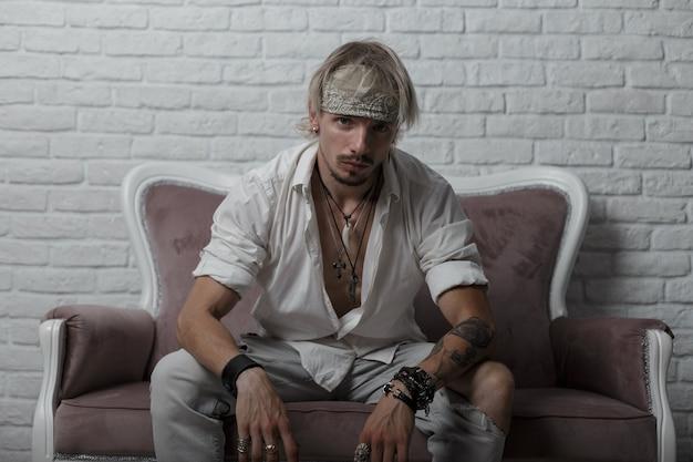 Junger attraktiver mann hipster in einem kopftuch mit einer stilvollen frisur mit einem tattoo mit armbändern in trendigen kleidern, die auf einem sofa sitzen