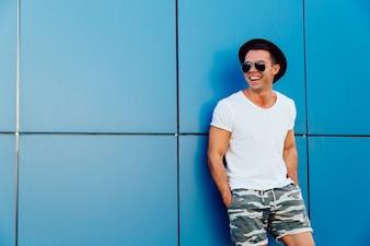 Junger attraktiver Mann in der Sonnenbrille, die auf dem blauen Wandhintergrund steht