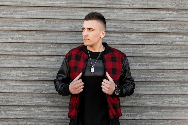 Junger attraktiver mann in der trendigen schwarz-rot karierten jacke in einem trendigen schwarzen t-shirt mit amulett, das nahe einer weinlese-holzwand an einem sommertag aufwirft