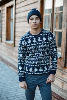 Junger attraktiver mann in einer strickmütze in einem blauen vintage-strickpullover mit einem weihnachtsmuster in jeans steht in der nähe eines alten hölzernen braunen hauses. hipster fashion guy.