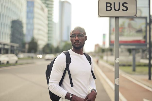 Junger attraktiver mann mit brille und rucksack, der tagsüber an der bushaltestelle steht