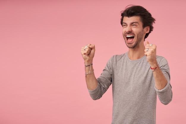 Junger attraktiver mann mit erhobenen fäusten, die mit weit geöffnetem mund beiseite schauen, in grauem pullover stehen und vor freude wahnsinnig sind