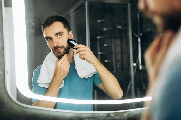 Junger attraktiver mann mit handtuch, der den spiegel betrachtet und sich früh morgens zu hause rasiert