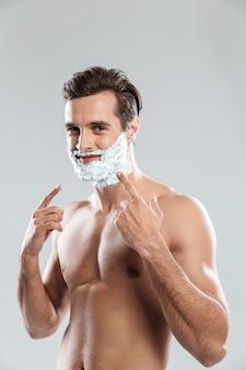 Junger attraktiver mann mit rasierschaum auf gesicht zeigend