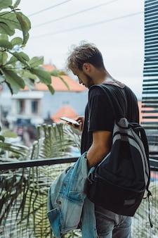 Junger attraktiver mann posiert in einem tropischen ort, auf einem hintergrund von palmen und grün