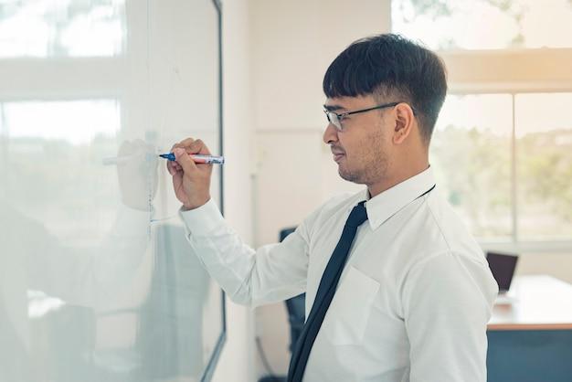 Junger attraktiver mann schreibt einen unternehmensplan auf whiteboard
