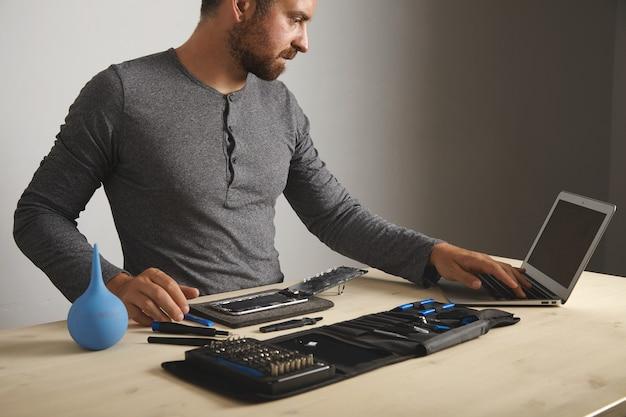 Junger attraktiver mann sieht führer im internet aus, während er sein smartphone wieder herstellt, bildschirm und batterie ändert