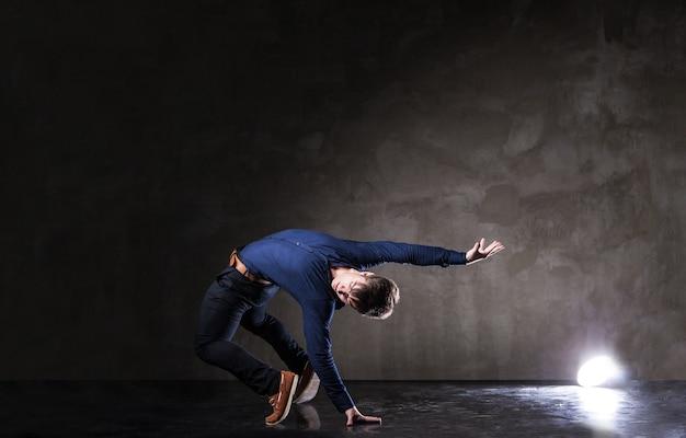 Junger attraktiver mann tanzt auf dunklem hintergrund
