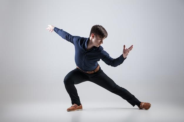 Junger attraktiver mann tanzt auf weißem hintergrund