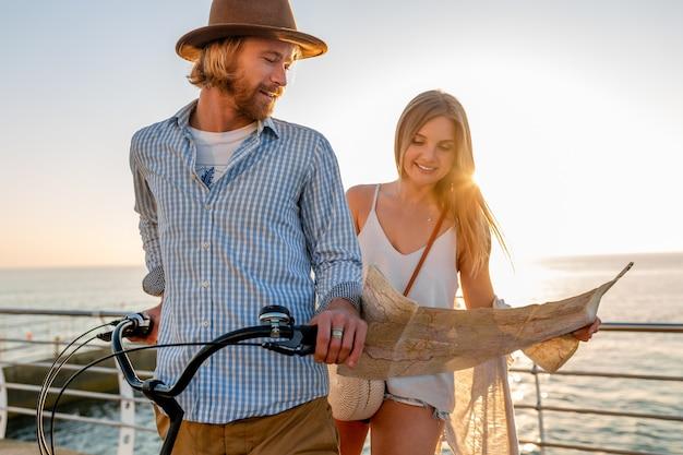 Junger attraktiver mann und frau, die auf fahrrädern reisen, romantisches paar in den sommerferien am meer bei sonnenuntergang, boho-hipster-stil-outfit, freunde, die spaß zusammen haben