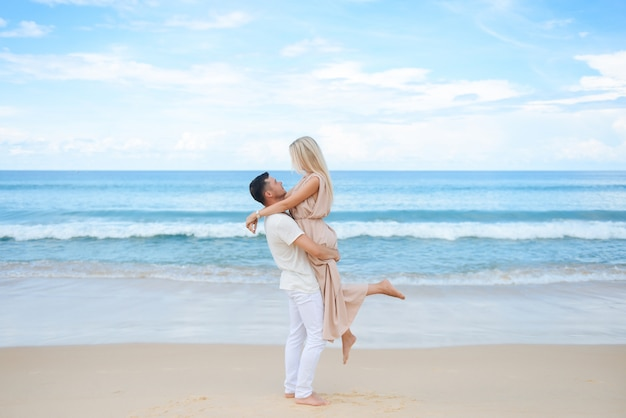 Junger attraktiver mann und frau in der liebe gehen und umarmen auf weißem sand und azurblauem meer. reisen, flitterwochen
