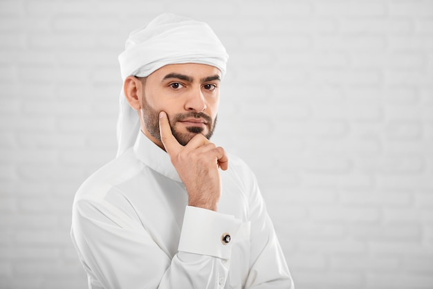 Junger attraktiver moslemischer mann im traditionellen islamischen klumpen, an etwas denkend