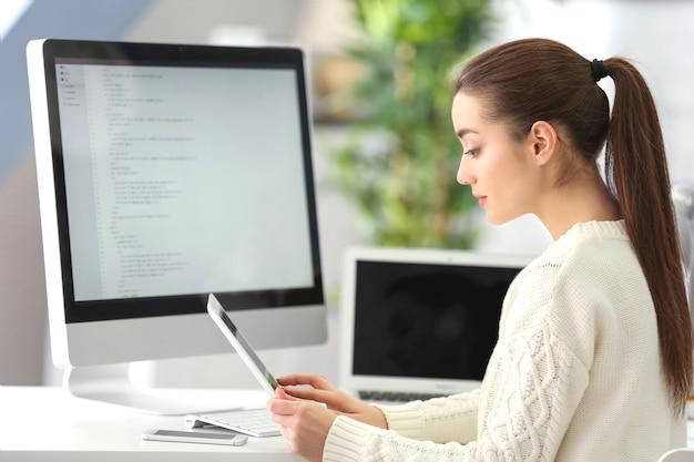 Junger attraktiver programmierer, der im büro arbeitet