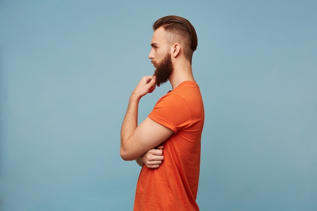 Junger attraktiver starker mann mit einem modischen haarschnitt dicken bart in einem roten t-shirt hält seine hand nahe seinem kinn