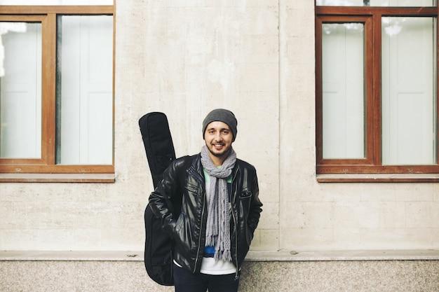 Junger attraktiver straßenkünstler mit seiner gitarre