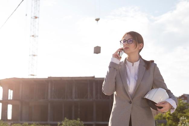 Junger attraktiver weiblicher architekt, der auf mobiltelefon an der baustelle spricht