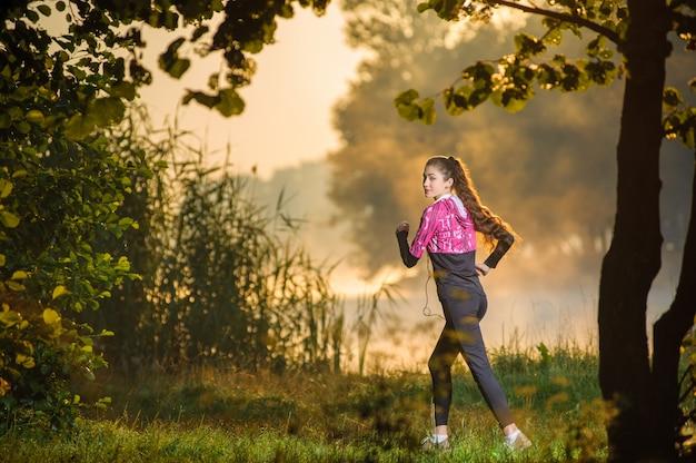Junger attraktiver weiblicher läufer, der in natur während des sonnenaufgangs läuft