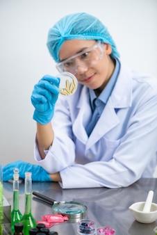 Junger attraktiver weiblicher wissenschaftler mit den schutzbrillen und maske, die eine transparente pille halten