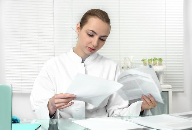 Junger attraktiver weiblicher wissenschaftler oder student im aufbaustudium liest wissenschaftliches papier