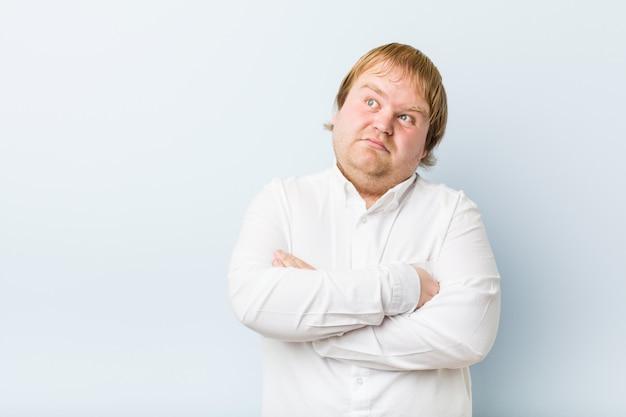 Junger authentischer dicker mann der rothaarigen, der in camera mit sarkastischem ausdruck unglücklich schaut.