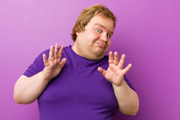 Junger authentischer dicker mann der rothaarigen, der jemand zeigt eine geste des ekels zurückweist.
