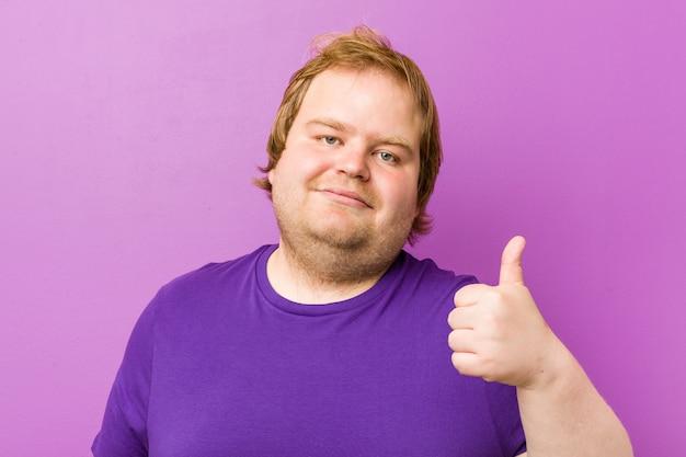 Junger authentischer dicker mann der rothaarigen, der oben daumen lächelt und anhebt