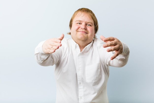 Junger authentischer dicker mann der rothaarigen fühlt sich überzeugt, der kamera eine umarmung gebend.