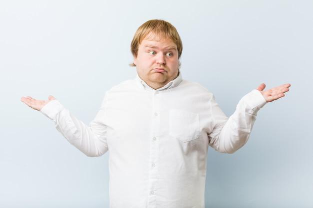 Junger authentischer dicker mann der rothaarigen verwirrt und zweifelhaft, schultern zuckend, um einen kopienraum zu halten.