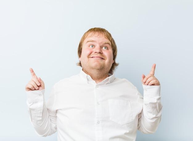 Junger authentischer dicker mann der rothaarigen zeigt mit beiden vorderen fingern an, eine leerstelle oben zu zeigen.