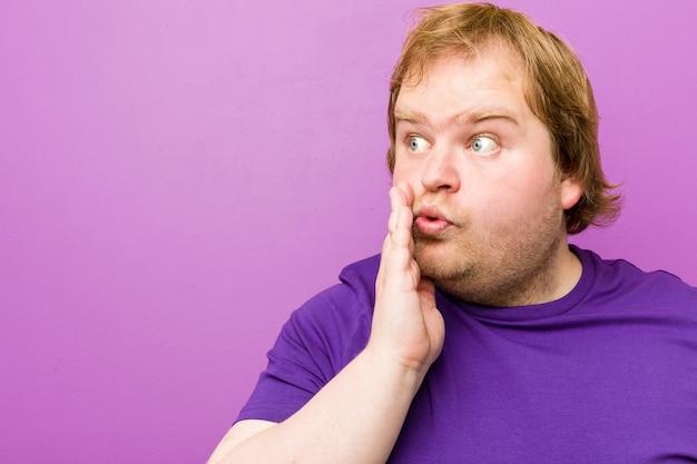Junger authentischer fetter mann der rothaarigen sagt geheime heiße bremsennachrichten und schaut beiseite