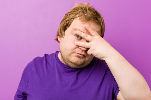 Junger authentischer rothaariger dicker mann blinzelt in die kamera durch finger, verlegenes bedeckendes gesicht.