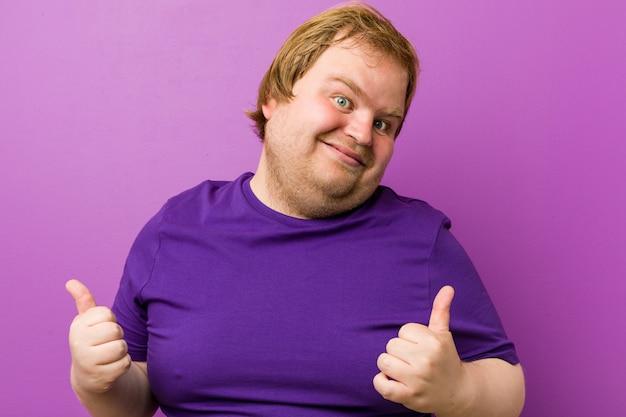 Junger authentischer rothaariger dicker mann, der beide daumen anhebt, lächelnd und zuversichtlich.