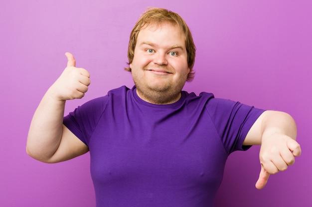 Junger authentischer rothaariger dicker mann, der daumen hoch und daumen runter zeigt, schwieriges konzept wählen