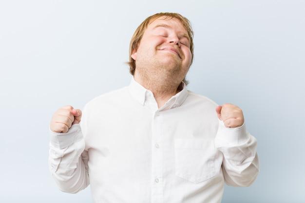 Junger authentischer rothaariger dicker mann, der faust hebt, sich glücklich und erfolgreich fühlt. siegeskonzept.