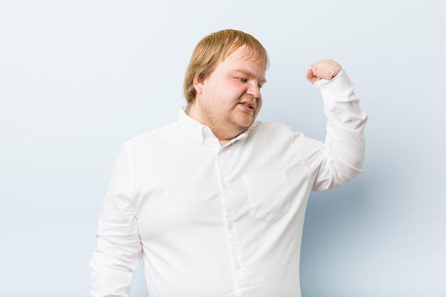 Junger authentischer rothaariger dicker mann, der faust nach einem sieg, siegerkonzept erhebt.