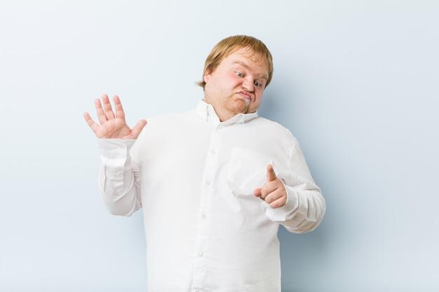 Junger authentischer rothaariger dicker mann, der jemanden ablehnt, der eine geste des ekels zeigt.