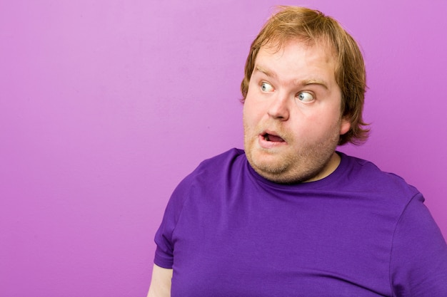 Junger authentischer rothaariger dicker mann, der wegen etwas geschockt wird, das sie gesehen hat.