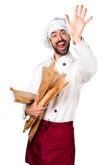 Junger bäcker hält brot und salut