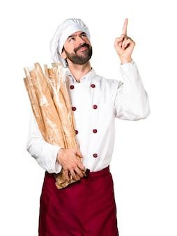 Junger bäcker hält brot und zeigt nach oben