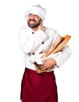 Junger bäcker hält etwas brot mit nackenschmerzen